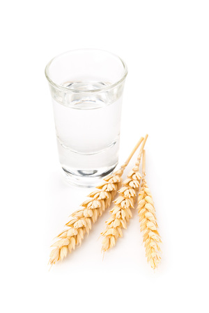 German hard liquor Korn Schnapps in shot glass with wheat ears over white background