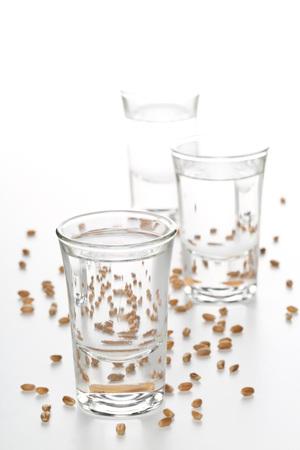 German hard liquor Korn Schnapps in shot glasses with wheat grains over white background Standard-Bild