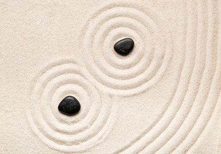 Zen sand and stone garden with raked lines, curves and circles. Simplicity, concentration or calmness abstract concept. Top view.