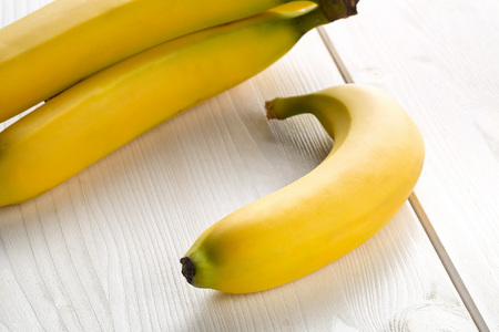 Bundle of fresh, yellow, ripe bananas on white wooden table Standard-Bild