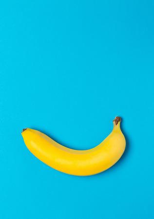 Single fresh, yellow, ripe banana over cyan background