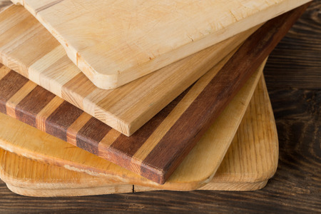 Stack of wooden cutting or chopping boards on kitchen table Standard-Bild