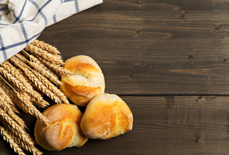 Bunch of whole, fresh baked wheat buns with wheat ears on dark wooden table top view from above with copy space