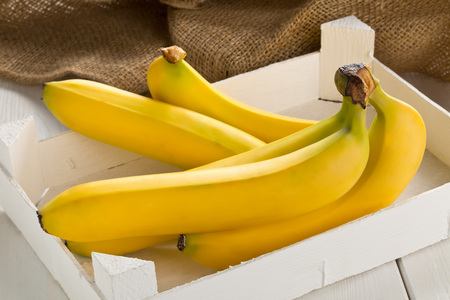 Bundle of fresh, yellow, ripe bananas in white wooden box on wood table with burlap sack