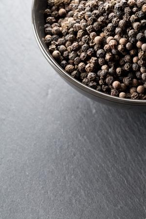 Raw, natural, unprocessed black pepper peppercorns in black bowl on dark stone background