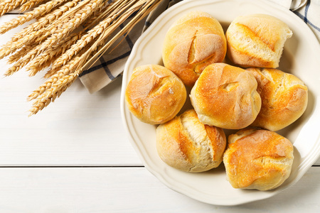 Bunch of whole, fresh baked wheat buns with wheat ears on plate on white wooden table top view from above with copy space