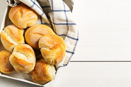 Bunch of whole, fresh baked wheat buns with wheat ears on tray on white wooden table top view from above with copy space