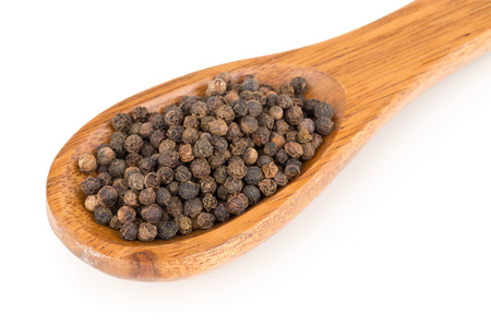 Heap of raw, natural, unprocessed black pepper peppercorns in wooden spoon over white background