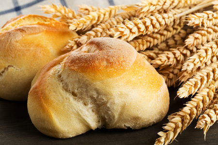 Bunch of whole, fresh baked wheat buns with wheat ears on dark wooden table in kitchen Standard-Bild