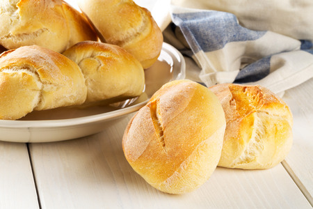 Bunch of whole, fresh baked wheat buns on plate with kitchen towel on white wooden table