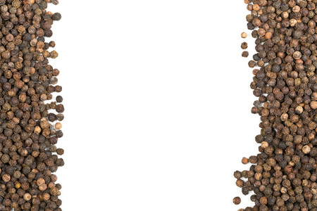 Frame of raw, natural, unprocessed black pepper peppercorns over white background