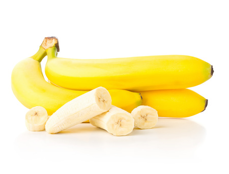 Bundle of fresh, ripe, yellow bananas with sliced banana pieces over white background