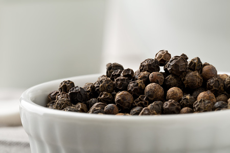 Raw, natural, unprocessed black pepper peppercorns white bowl on kitchen table