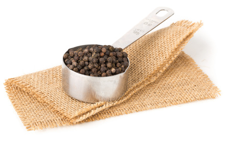 Raw, natural, unprocessed black pepper peppercorns in measuring cup on white background