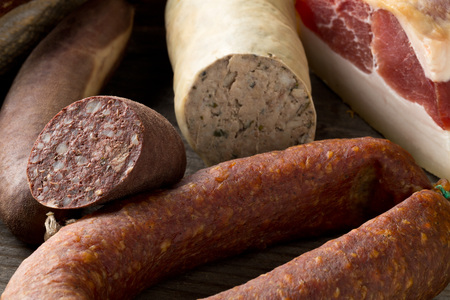 Assortment of german sausage specialties hard cured salami, liver sausage (Leberwurst), blood sausage (Blutwurst) and bacon on kitchen table Standard-Bild