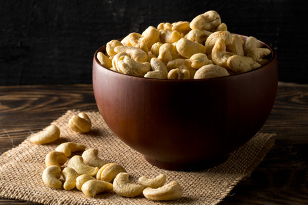 Heap of raw, organic, whole cashew nut kernels in wooden bowl on table over dark background