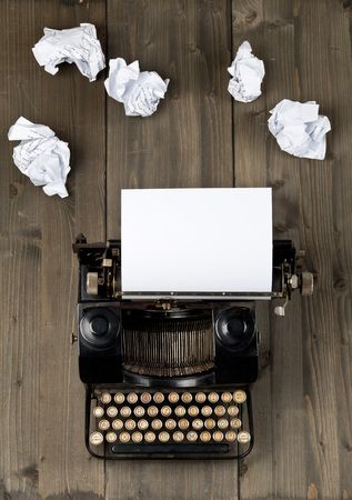 Vintage typewriter top down flatlay shot from above with empty, blank sheet of paper and crumbled paper balls on wood table background