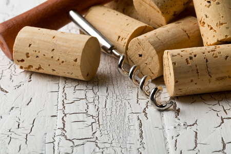 Heap of unused, new, brown natural wine corks with corkscrew on white wooden board background