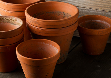 Group of empty, used terracotta planting pots on wooden table background