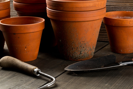 Group of empty, used terracotta planting pots on wooden table background with gardening tool and gardening shovel