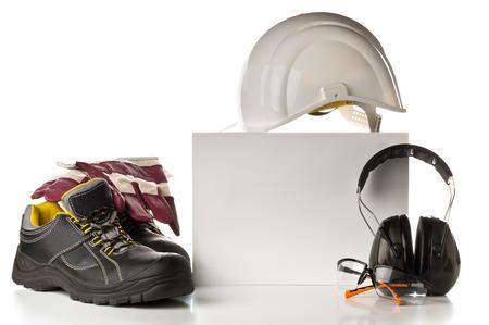 Équipement de sécurité et de protection au travail - chaussures de protection, lunettes de sécurité, gants et protection auditive sur fond blanc avec carte vierge pour copie
