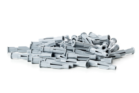 Heap of unused, new, grey plastic wall plug bolts over white background Stok Fotoğraf