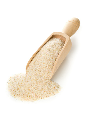 Heap of psyllium husk in wooden scoop over white background. Psyllium husk also called isabgol is fiber derived from the seeds of Plantago ovata plant found in India. Stock Photo