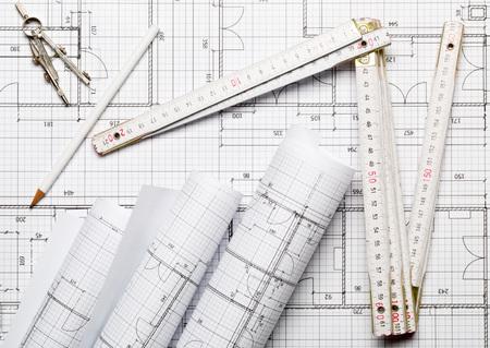 Rollen von architektonischen Blaupausenhausbauplänen auf Blaupausenhintergrund mit Zollstock, Bleistift und Zirkel auf Tisch-Flatlay-Draufsicht von oben