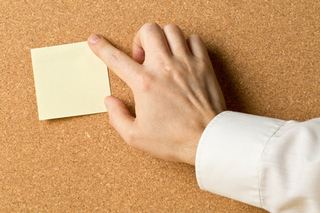 Business man pinning empty yellow sticky paper memo note on cork board with copy space