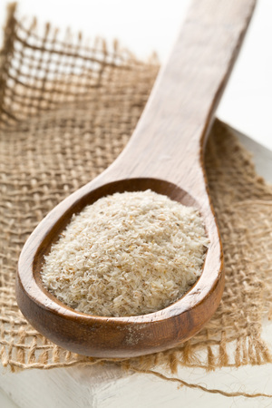 Heap of psyllium husk in wooden spoon on burlap. Psyllium husk also called isabgol is fiber derived from the seeds of Plantago ovata plant found in India. Selective focus. Stock Photo