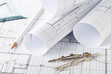 Rollos de planos de construcción de casas de planos arquitectónicos sobre fondo de planos en mesa con lápiz, cuadrado y brújulas Foto de archivo