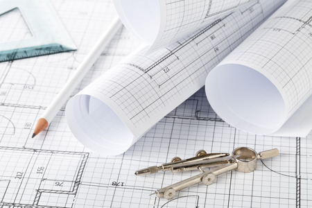 Rolls of architectural blueprint house building plans on blueprint background on table with pencil, square and compasses