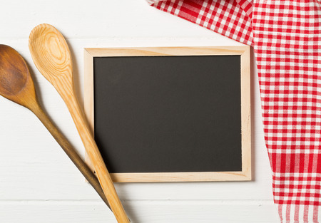 Blank, empty, black chalkboard with wooden cooking spoons and red checkered dish towel flat lay from above on white wooden table with copy space