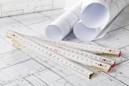 Rolls of architectural blueprint house building plans with folding rule on blueprint background on table Stockfoto