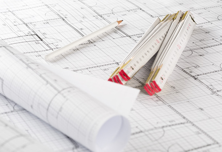 Rolls of architectural blueprint house building plans on blueprint background on table with pencil and folding rule