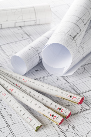Rolls of architectural blueprint house building plans with folding rule on blueprint background on table Stock fotó