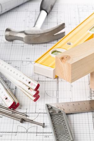 Bauwerkzeuge und Holzleisten auf dem Bauplan des Bauhauses auf dem Tisch Standard-Bild
