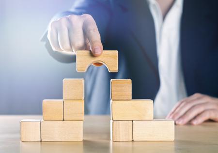 Geschäftsmann, der die Lücke zwischen zwei Türmen oder Parteien aus Holzblöcken überbrückt; Konfliktmanagement- oder Mediatorkonzept, blau getönt mit Lichtreflexen