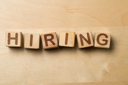 Hiring written on wooden cube blocks on wooden office table - human resources or job vacancy concept