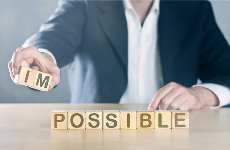 Business man puts away first two letters from the word impossible, so it becomes possible; management or solution finding concept, blue toned with ligth flare