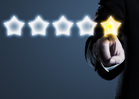 Business man in suit pointing at five star rating stars, selecting top rating; blue background Stock Photo
