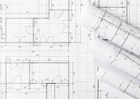 Rollen von architektonischen Blaupausenhausbauplänen auf Blaupausenhintergrund auf Tisch-Flatlay-Draufsicht von oben