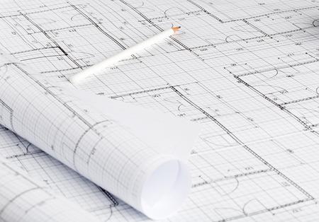 Rollen von architektonischen Blaupausenhausbauplänen auf Blaupausenhintergrund auf dem Tisch mit Bleistift Standard-Bild