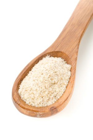 Heap of psyllium husk in wooden spoon over white background. Psyllium husk also called isabgol is fiber derived from the seeds of Plantago ovata plant found in India.