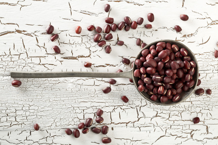 Raw, uncooked, dried adzuki (red mung) beans in metal spoon on white rustic wood table background top view flat lay from above