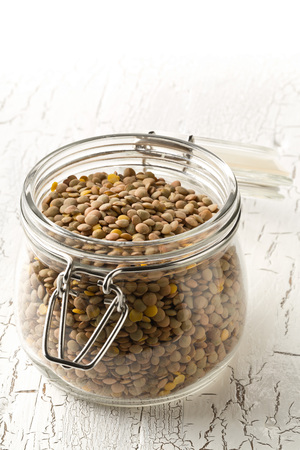 Raw, dry, uncooked brown lentil legumes in glass storage jar on white wood table background with selective focus