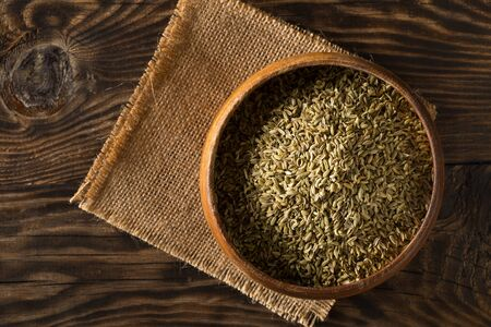 Dried fennel seeds in wooden bowl on rustic wooden table background top view flat lay from above with selective focus Reklamní fotografie