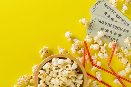 Movie tickets, soda drink plastic straws and popcorn on yellow table background. Home theatre movie or series night concept. Flat lay top view from above with copy space. Archivio Fotografico