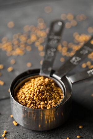 Dried, raw fenugreek seed in measuring scoop on dark moody black kitchen table background with selective focus