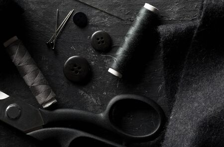 Flat lay top view sewing tools with buttons, textile fabric, thread, needles and scissors on black dark wooden table Stok Fotoğraf